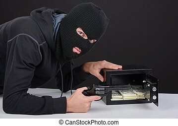 Criminality - Thief burglar stealing money during home safe...