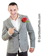 man in suit pointing at rose in his pocket