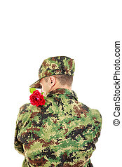 Soldier with turned back holding red rose over shoulder with...