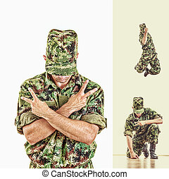 soldier with hidden face in green camouflage uniform jumping...