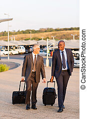businessmen walking in airport parking lot - smart...