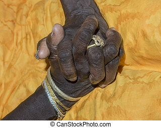 Hands of an old lady joined on her yellow dress