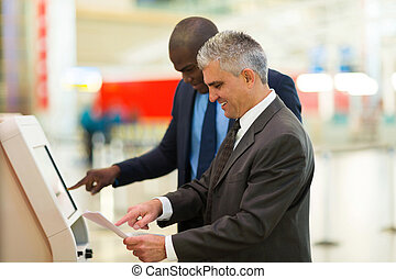business travellers using self help check in machine at...