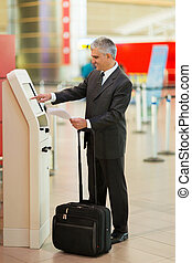 middle aged businessman using self help check in machine