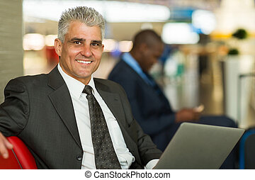 middle aged man waiting at airport lounge - handsome middle...