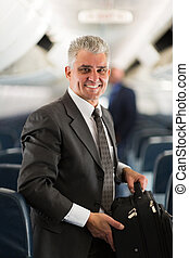 middle aged businessman carrying bag on airplane - good...