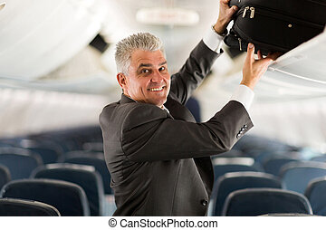 middle aged business traveler putting luggage into overhead...