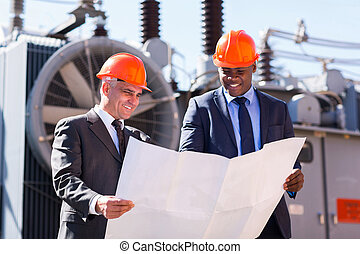 power plant managers holding blueprint
