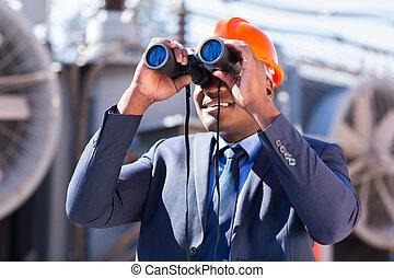 african electrician engineer using binoculars looking at...