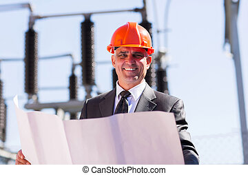 middle aged electrical manager with blueprint - good looking...