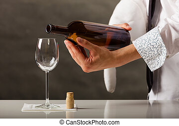 Man waiter pouring wine into glass. - Male waiter or butler...