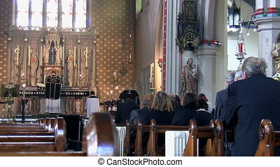 Funeral mass in the church - People and priest praying at...