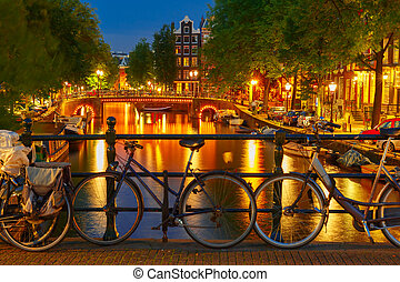 Night illumination of Amsterdam canal and bridge with...