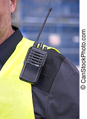 walkie-talkie on shoulder of man i yellow vest