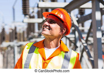 mature male electrician in electrical substation - smiling...