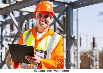 middle aged electrician holding clipboard