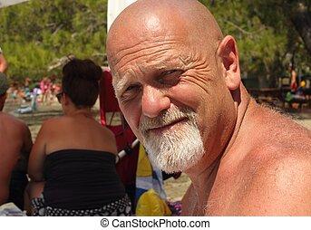 An englishman with a bald head and a beard on a beach