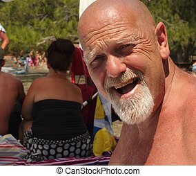 An englishman with a bald head and a beard on a beach
