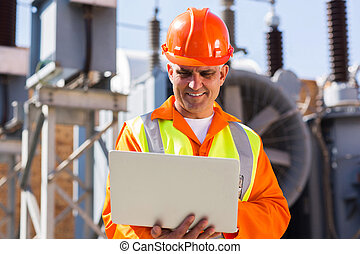 mid age engineer using laptop computer in power plant - mid...