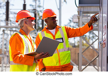 male engineers working in electrical substation - two male...