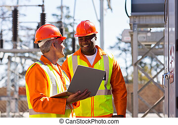 electricians using laptop computer in substation - happy...