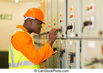 african american technician writing down machine setting data