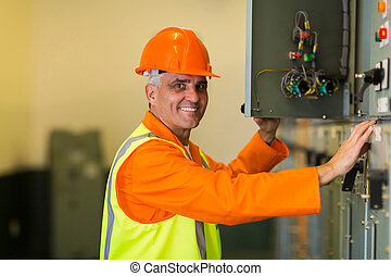 mid age electrician checking industrial control box - happy...