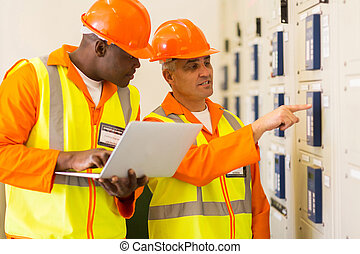 two electricians checking industrial control box