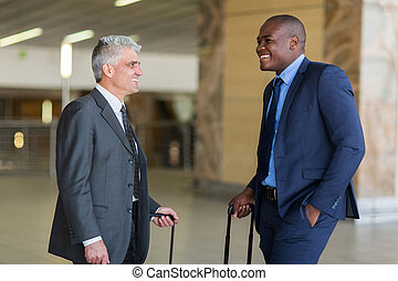two businessmen talking at airport - two friendly...