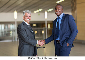 business travellers greeting at airport - portrait of...
