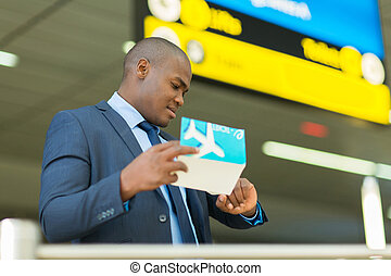 african american business traveller checking time -...