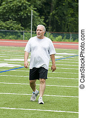 middle age man exercising on sports field - overweight...