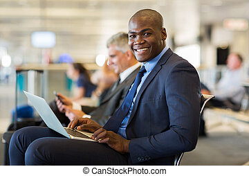 african business traveller with laptop computer - happy...