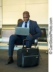 african businessman using tablet computer at airport - smart...