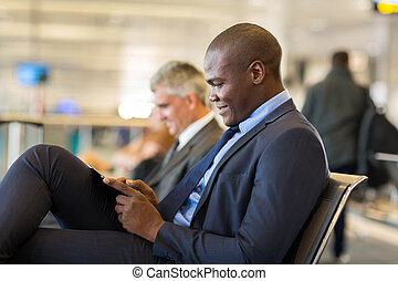 african businessman using tablet computer at airport -...