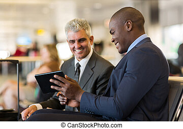 business travelers using tablet computer at airport