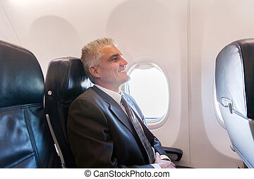 middle aged airplane passenger relaxing on air plane - happy...