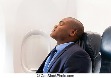 african businessman resting on airplane - handsome african...