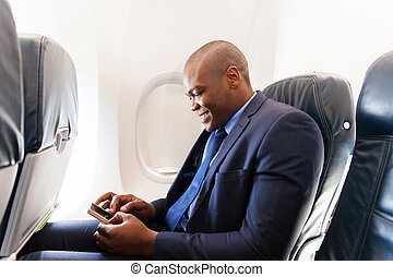 african airplane passenger using smart phone on plane -...