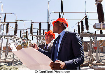 managers working in electric substation - industrial...