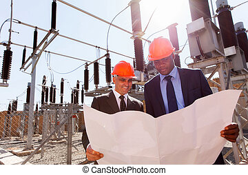 power company managers discussing blueprint