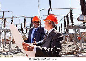 businessmen working in power plant - two businessmen working...