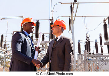 two businessman handshaking in substation - two cheerful...