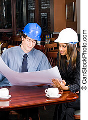construction business meeting - two businesspeople wearing...