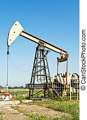 view of pumpjack pumping oil in summer day