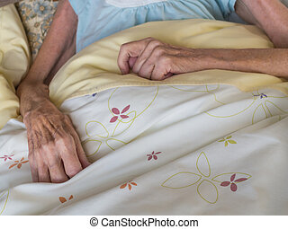 Old woman in a bed - Skinny arms and hands of a very old...