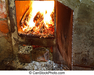 flame of burning wood in furnace with open door