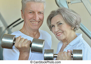 Senior couple exercising with dumbbells - Portrait of a...