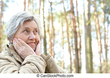 Pensive senior woman walking in the forest in autumn