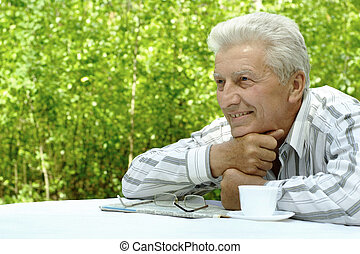older man reading newspaper - Attractive smiling older man...